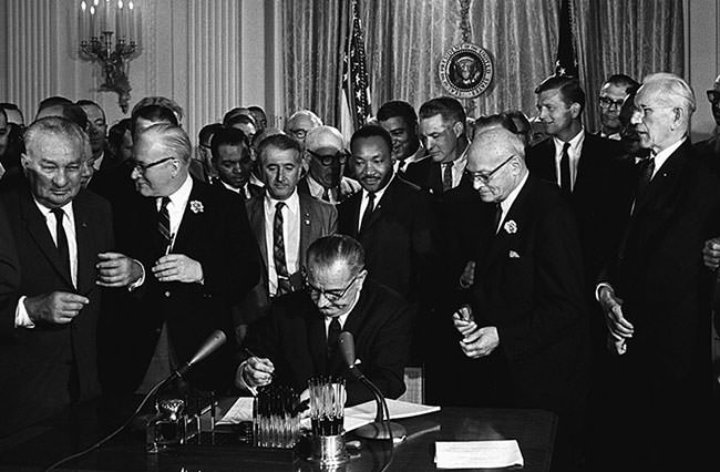 Lyndon B. Johnson signs the Civil Rights Act of 1964