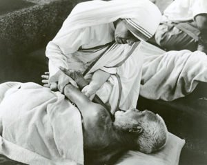Mother Teresa taking care of a sick-man